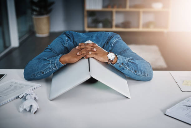 I refuse to face any more deadlines Shot of a businessman lying down on a desk with a laptop over his head in an office face down stock pictures, royalty-free photos & images