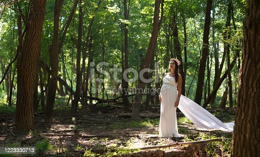 Pregnant woman in white gown stands in a ray of sun in the forest