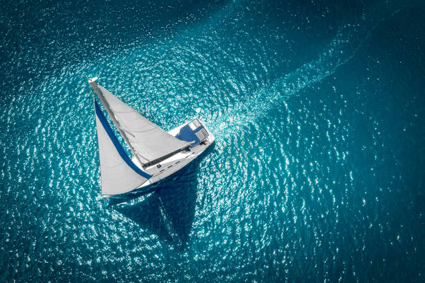 regatta sailing ship yachts with white sails at opened sea. aerial view of sailboat in windy condition - sail stock pictures, royalty-free photos & images