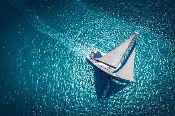 Regatta-Segelschiffyachten mit weißen Segeln auf offenem Meer. Luftaufnahme des Segelbootes in windigem Zustand – Foto