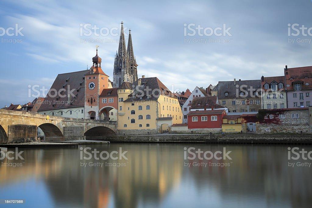 Regensburg skyline reflected on water under the bridge stock photo