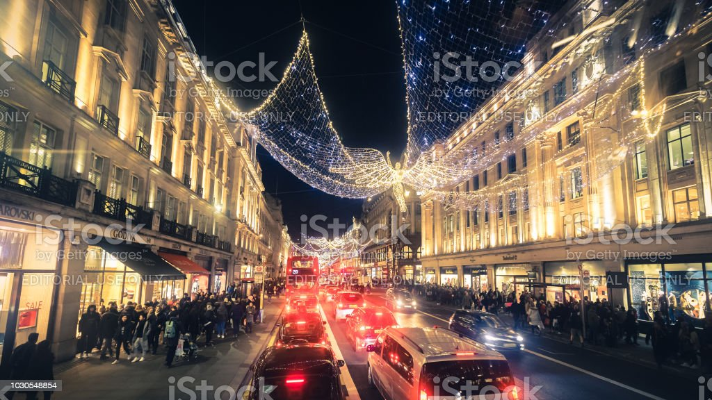 Regent Street angels holiday lights with crowds of shoppers in...