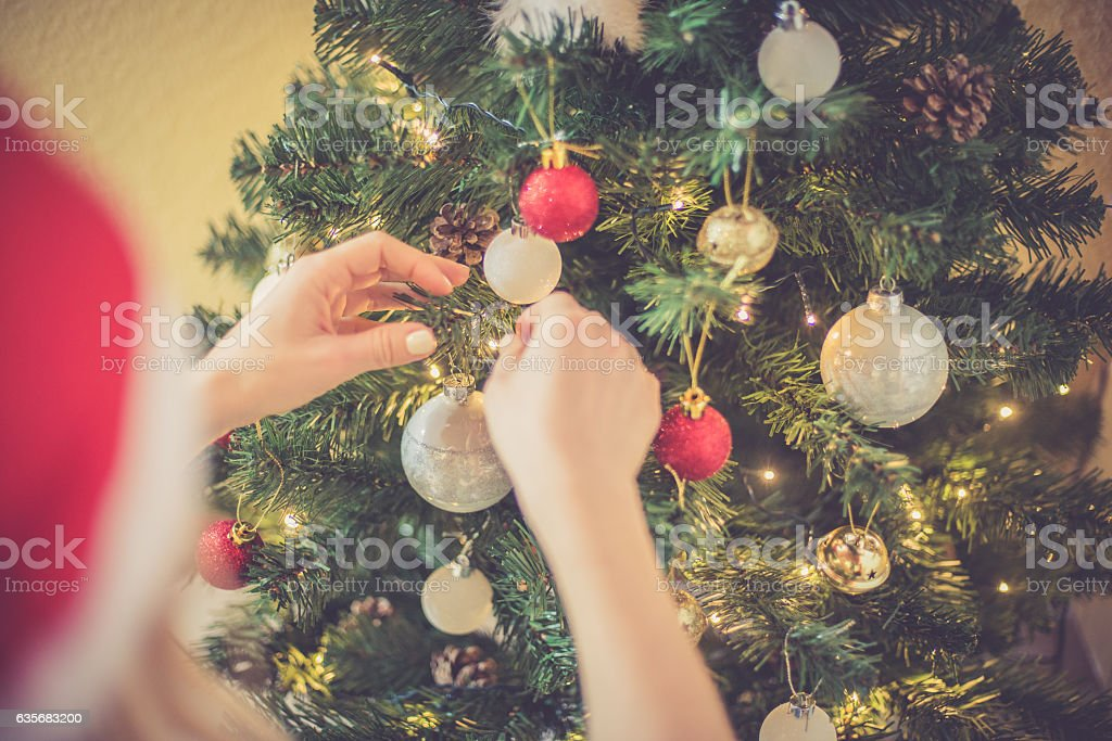 Regional Christmas at home - Blonde Woman decorating Xmas tree stock photo