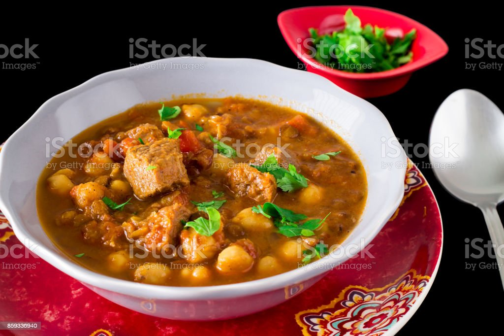 Regional Food Backgrounds. Famous Moroccan soup harir with meat, chickpeas, lentils, tomatoes and spices. Dark photo stock photo