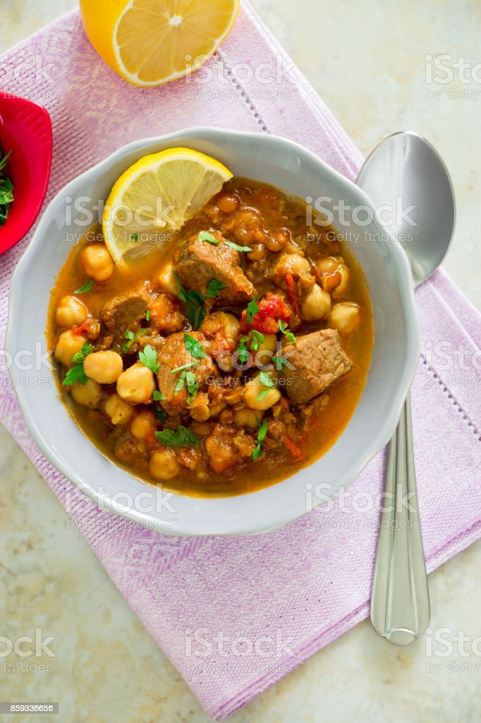Regional Food Backgrounds. Famous Moroccan soup harira with meat, chickpeas, lentils, tomatoes and spices. Hearty, fragrant. Preparing for Iftar in the holy month of Ramadan stock photo