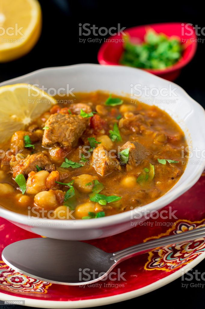 Regional Food Backgrounds. Famous moroccan soup harira with meat, chickpeas, lentils, tomatoes and spices. Dark vertical photo stock photo