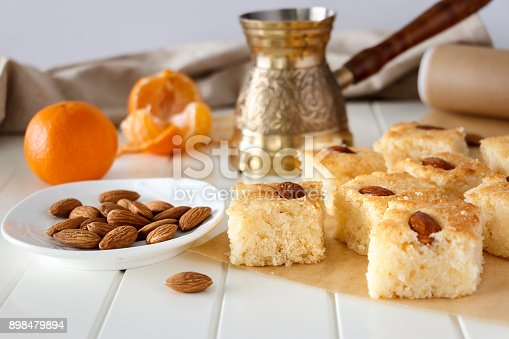 istock Regional Food Backgrounds.  Still life Pieces Basbousa (namoora) traditional arabic semolina cake with almond nut and syrup, orange and cooper jezva. Copy space. Selective focus. 898479894
