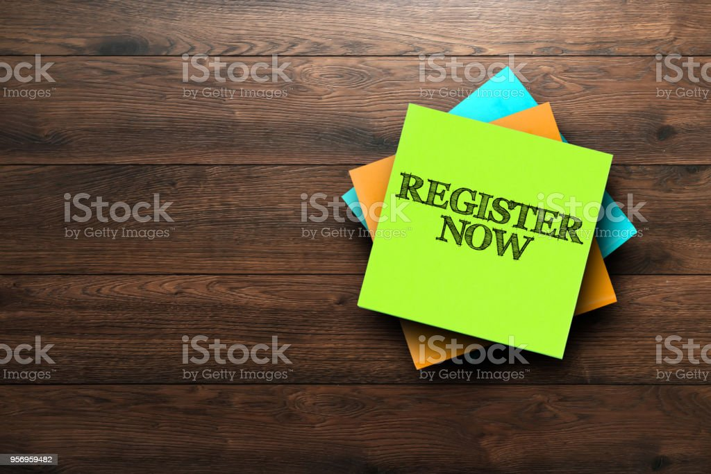 Register Now, the phrase is written on multi-colored stickers, on a brown wooden background. Business concept, strategy, plan, planning. stock photo