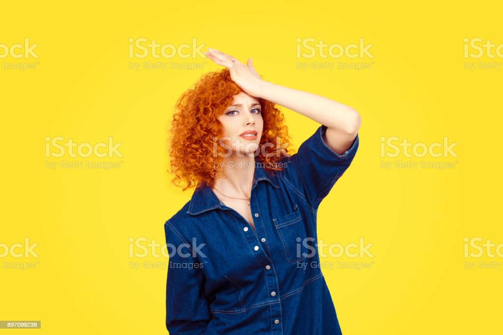 Regrets wrong doing. Closeup portrait silly young redhead curly woman slapping hand on head having duh moment isolated yellow background Negative human emotion facial expression body language reaction stock photo