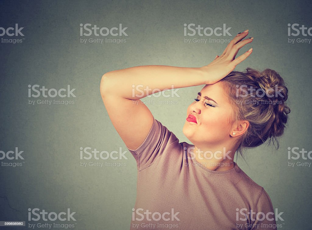 Regrets wrong. Silly woman slapping hand on head stock photo