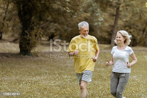 Joyful Senior Couple in Sportswear Running Outdoors in a Park on a Beautiful Spring Day Living Active Healthy Lifestyle