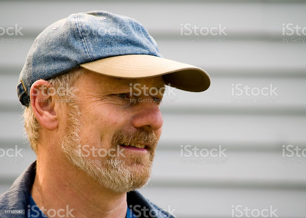 A regular guy who is wearing a blue baseball cap royalty-free stock photo