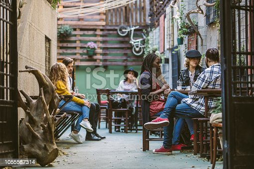 People Chatting and Drinking Coffee at Cozy Artistic Sidewalk Cafe