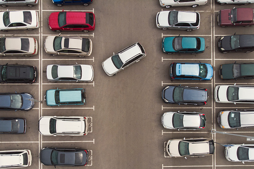 Regularity in auto parking. A view to the carefully parked ranks of cars. Car navigation in the motor park. Searching for vacant space for parking. The park is jammed with cars. Parking problems.