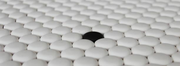 regularly arranged white go stones around only black stone stock photo