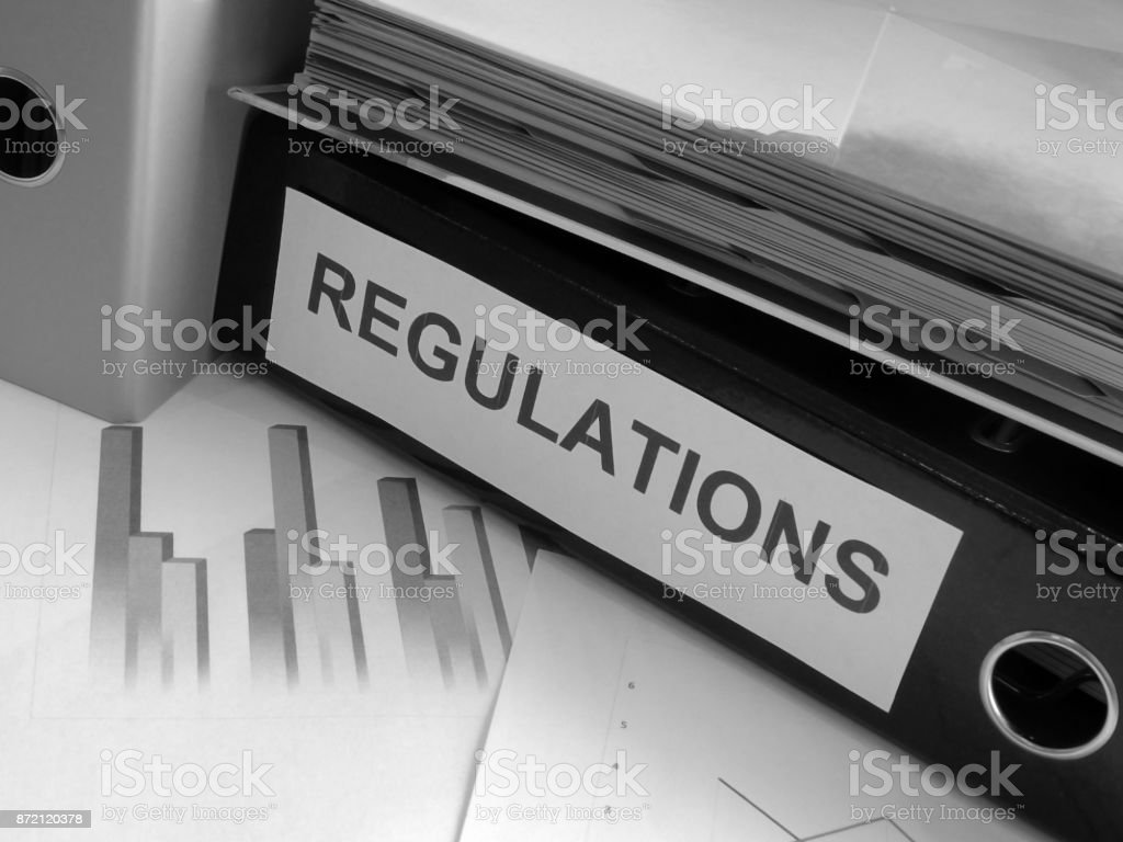 Regulations Folder on Cluttered Desk (Black and White) stock photo