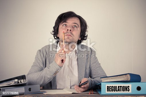 464906632 istock photo Regulations text on the binder, worried bussinesman thinking by the work desk 927776086