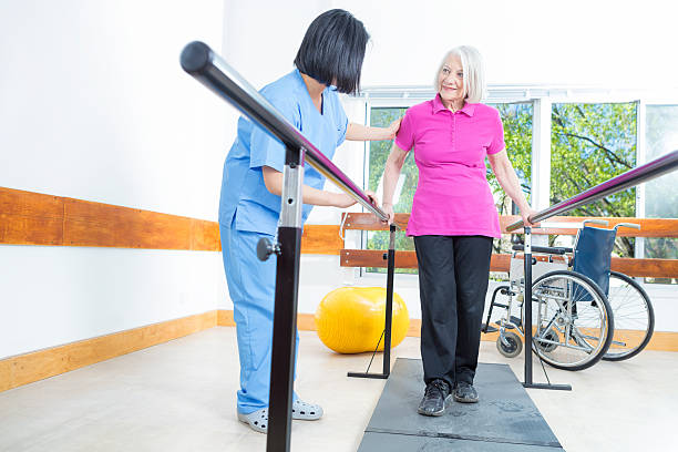 Rehabilitation clinic with elderly people and nurse stock photo