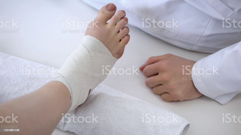 Rehabilitation specialist bandaging sprained ankle after running...