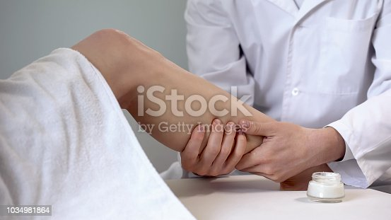 Rehabilitation specialist uses cream for leg massage, recovery after sprain