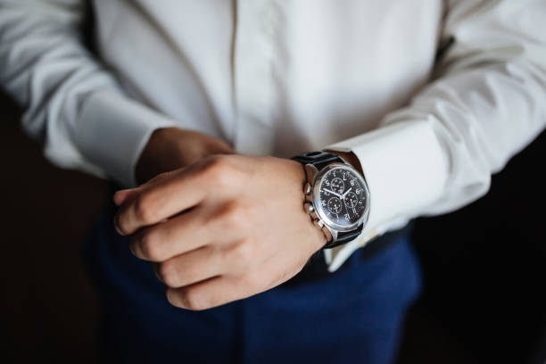Rehearsal preparation. Groom's watches on hand. High angle view of groom, Fixing his watches before wedding. stock photo