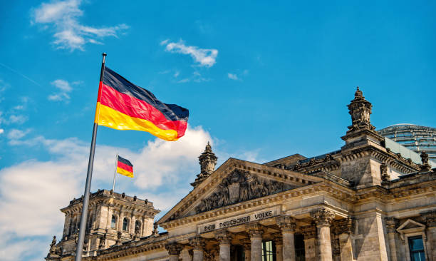 Reichstag building, seat of the German Parliament German flags waving in the wind at famous Reichstag building, seat of the German Parliament Deutscher Bundestag , on a sunny day with blue sky and clouds, central Berlin Mitte district, Germany germany stock pictures, royalty-free photos & images