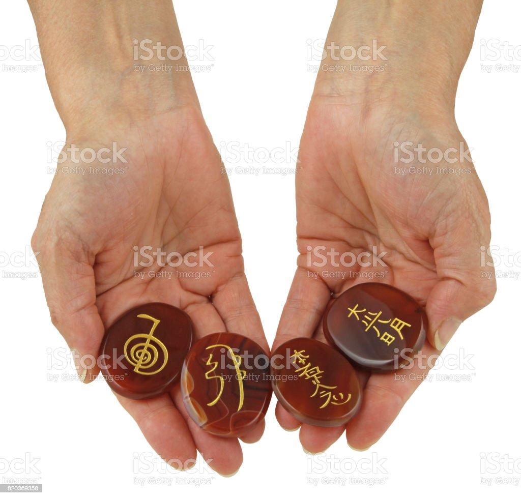 Reiki Symbols etched onto polished Carnelian stones stock photo