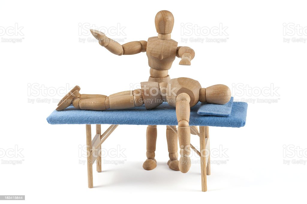 Reiki - wooden mannequin gets a therapie with healing hands stock photo