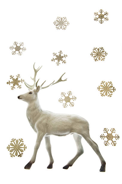 Reindeer figurine and snowflakes stock photo