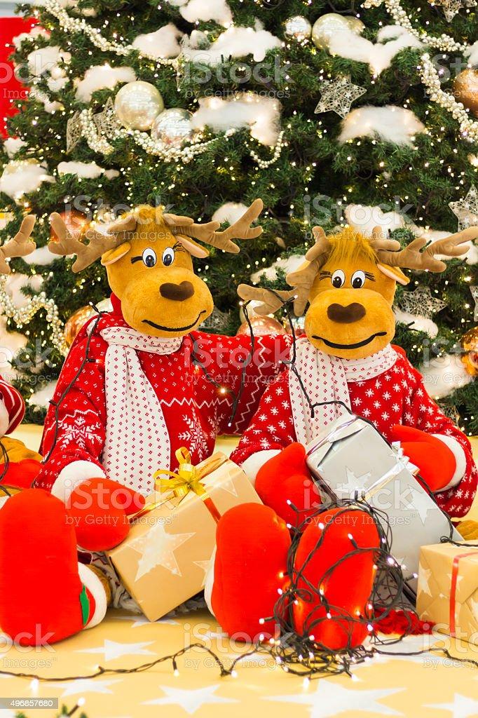 Reindeer preparing Christmas tree lights and presents stock photo