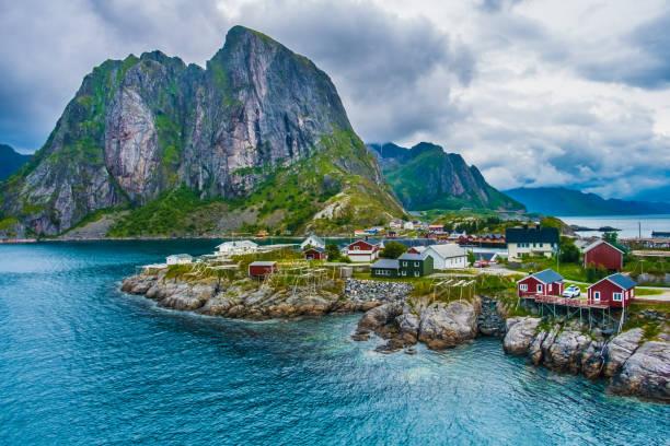 Reine, Lofoten-Inseln, Nordland, Norwegen. Das Hotel liegt nördlich des Polarkreises. Bekannt für seine natürliche Schönheit, unverwechselbare Landschaft mit dramatischen Bergen und Gipfeln, offene Meer und geschützte Buchten, Strände und unberührte Gebiete sowie malerische malerische villa – Foto