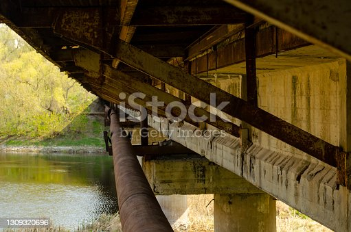 Reinforced concrete bridge dilapidated pillars. Overpass seen from below showing support beams