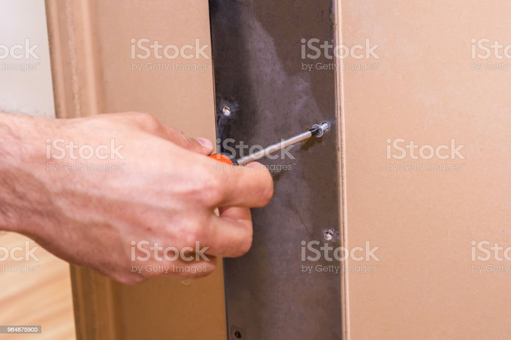 reinforcing the table with a metal plate using a screwdriver and a screw royalty-free stock photo