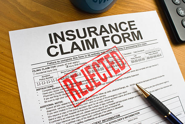 Rejected Insurance Claim Form Insurance Claim Form on a desktop stamped in red