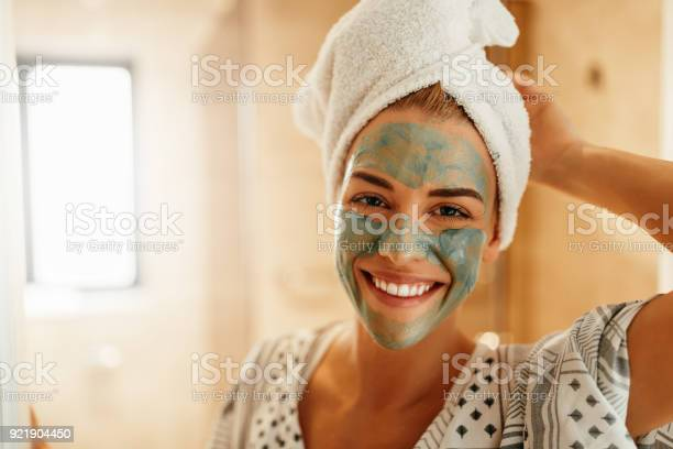 Portrait of an attractive young woman standing in the bathroom with a facial mask
