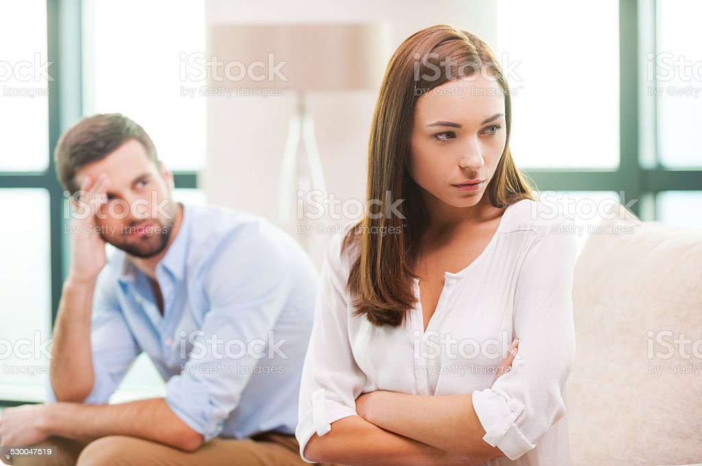 Relationship difficulties. Depressed young woman keeping arms crossed and looking away while man sitting behind her on the couch Adult Stock Photo