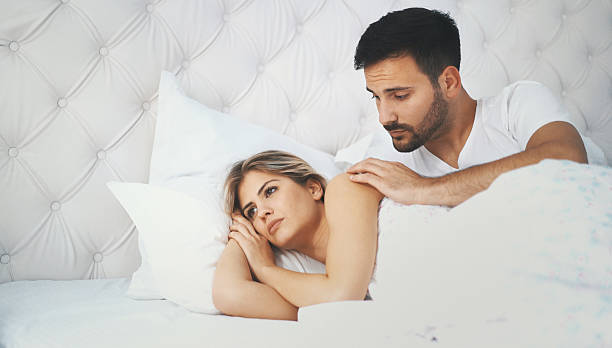 Relationship difficulties. Closeup dolly shot of a late 20's couple in bed having some relationship problems. As usual she's the one that got mad for almost no reason and he's trying to sort thing out. couple in bed stock pictures, royalty-free photos & images