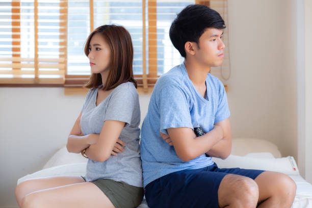 Relationship of young asian couple having problem on bed in the bedroom at home, family having conflict argument with unhappy, man and woman with issue, failure and stress together. stock photo