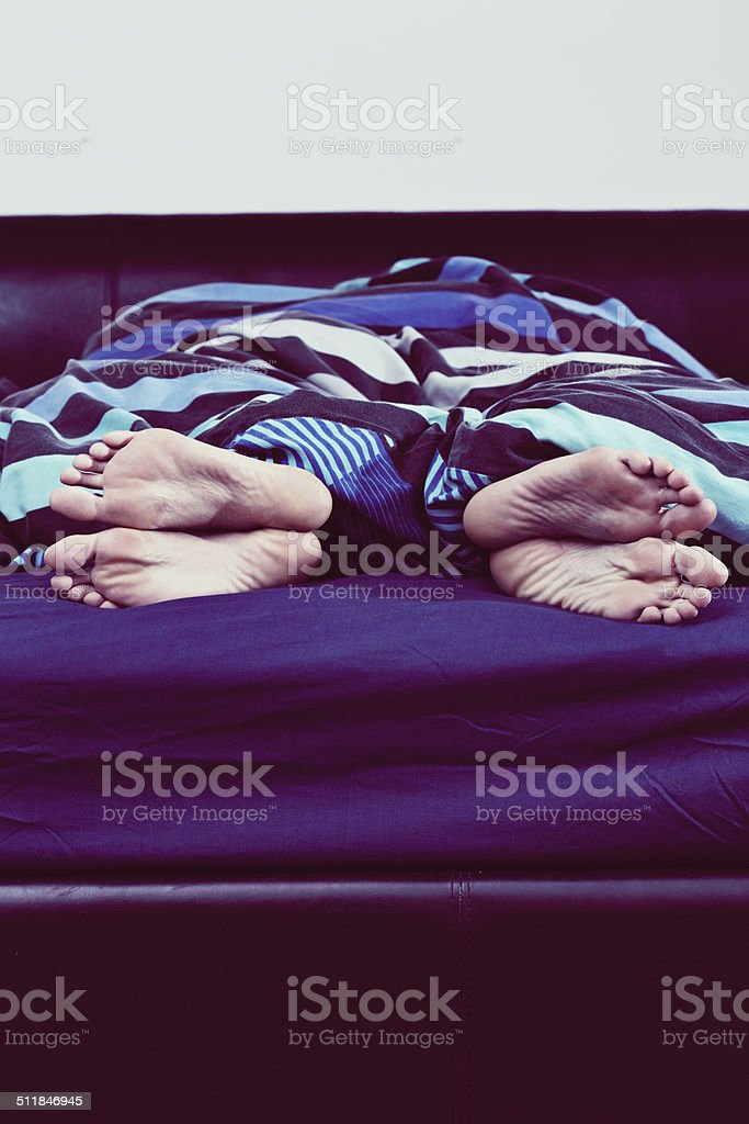 Relationship trouble? Feet of couple turned away from one another The bare feet, one pair male, one pair female, of a couple sleeping in bed, turned away from each other. Could indicate problems in the relationship. Copy space on sheet. Adult Stock Photo