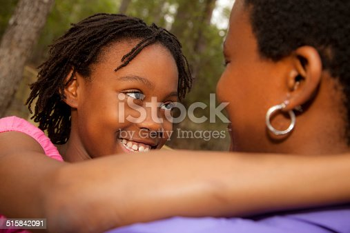 1091098026istockphoto Relationships: African descent mother and daughter hug outside. 515842091