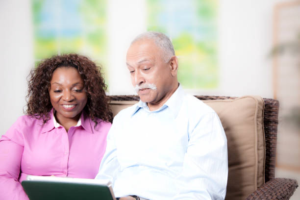 Relationships:  couple at home on couch Couple using a digital tablet to communicate with family and friends during stay at home order. covid stock pictures, royalty-free photos & images