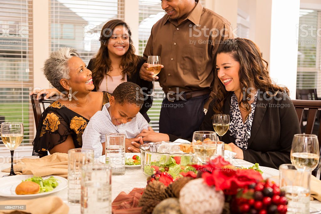 Multi-ethnic group of family and friends gather together at...