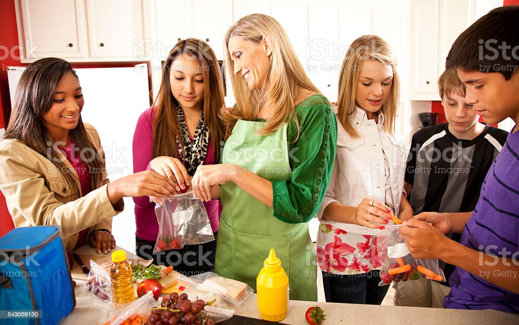 Relationships: Foster home teens, mom in kitchen making lunches. stock photo