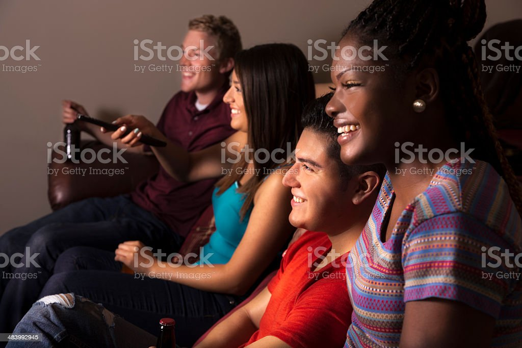 Relationships: Four friends hang out and watch TV. stock photo