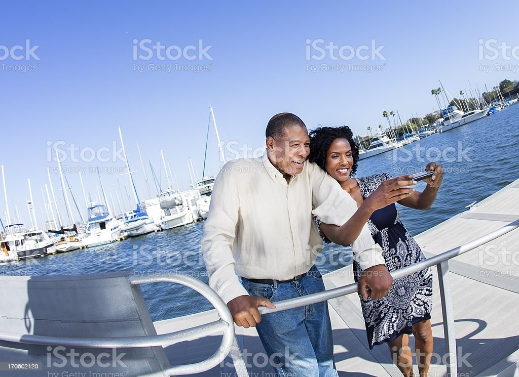 Relationships: Mature couple taking pictures on pier. Marina background. stock photo