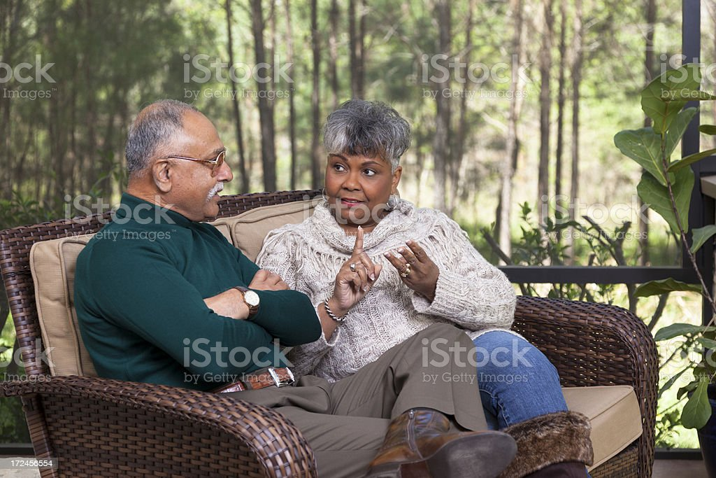 Relationships: Senior couple on screened porch arguing royalty-free stock photo