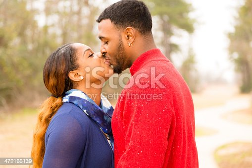 Young adult, African descent couple kiss outside in local park. Sidewalk, trees in winter or fall season.  Valentine's Day romance.