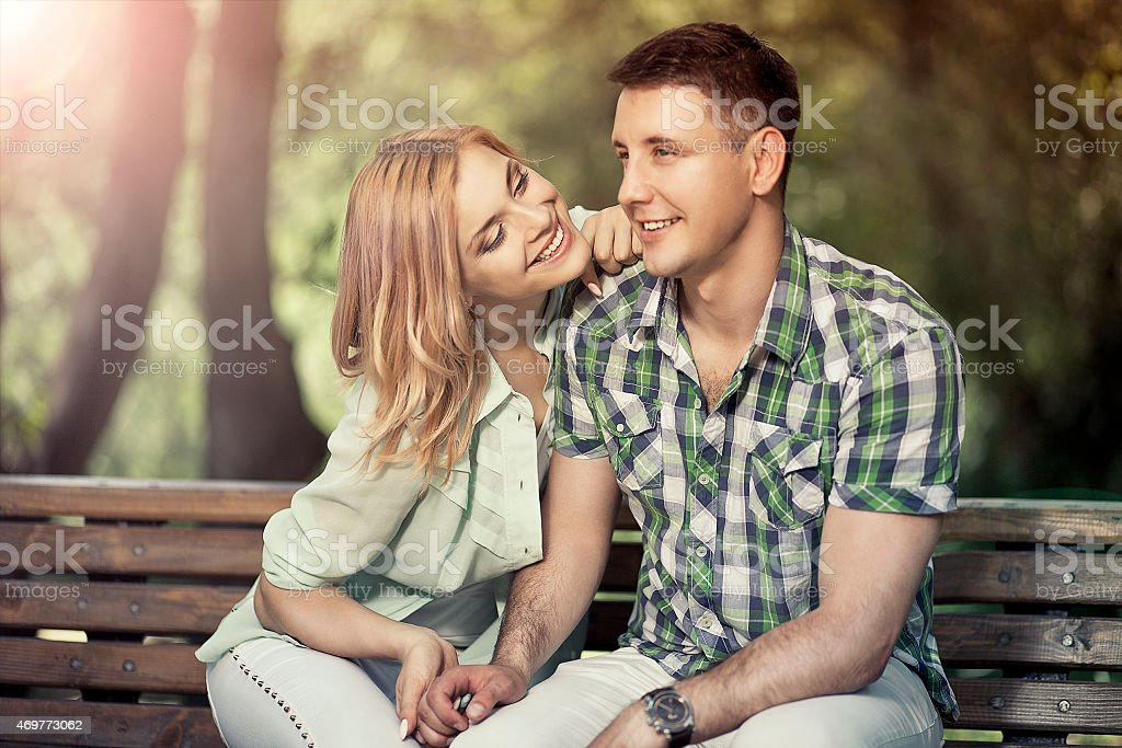 Relatioship concept. Happy young couple sitting in the park, smi stock photo