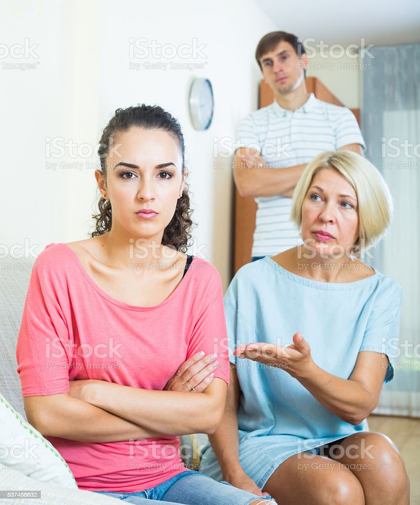 Relatives quarrelling with young woman in domestic interior stock photo