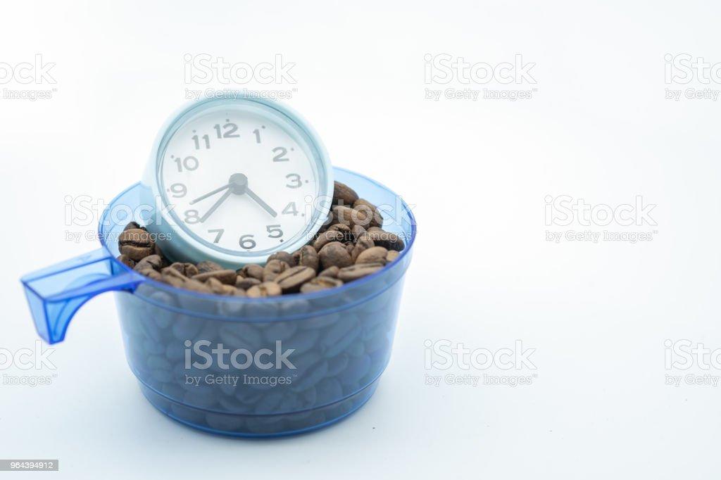 Ontspannen en tijd concept.  Close up van vintage ronde klok in kunststof kopje koffie volledig vullen met koffieboon op witte achtergrond. - Royalty-free Alarm Stockfoto